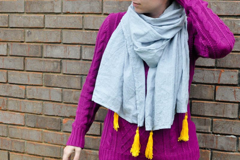 girl wearing scarf with tassels against brick wall