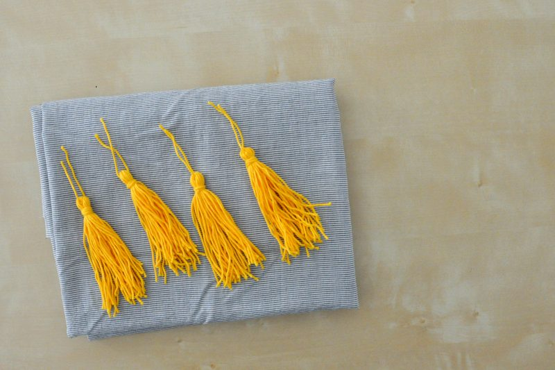 gold tassels laying on striped fabric